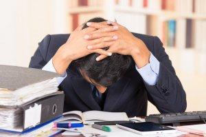 gestresster Büroarbeiter mit Bergen von Akten